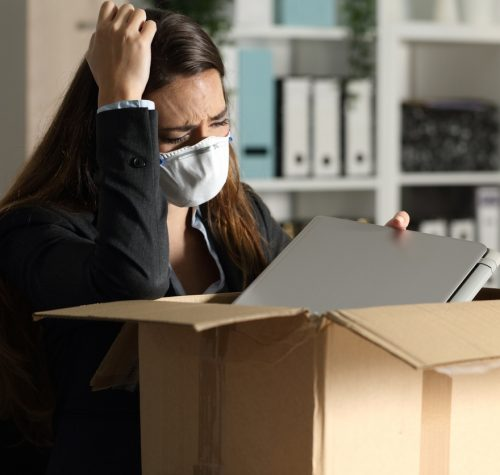 Fired executive woman with protective mask packing personal belongings on a box at the office at night